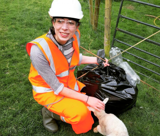 Jess Cole on site with a lamb